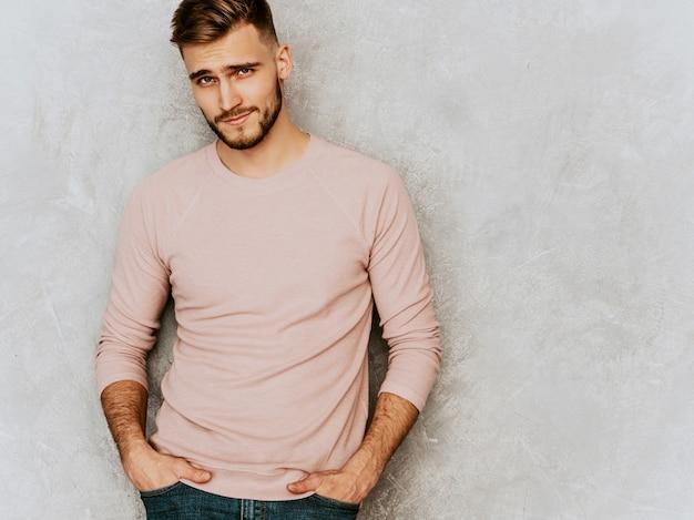 カジュアルな夏のピンクの服を着てハンサムな笑みを浮かべて若い男モデルの肖像画。ファッションスタイリッシュな男のポーズ