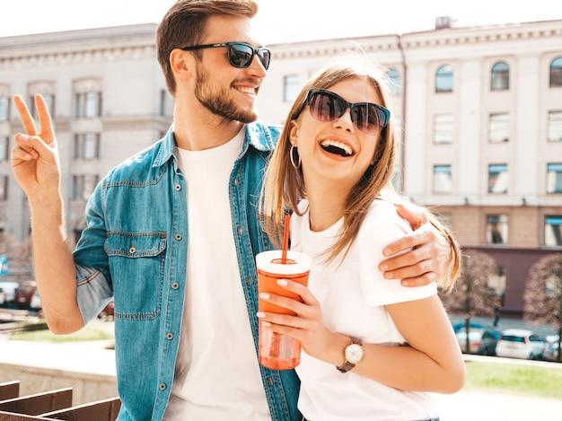 Портрет улыбается красивая девушка и ее красивый парень в повседневной летней одежды. , с бутылкой воды и соломы