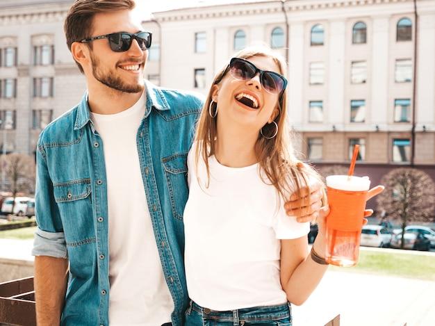 笑顔の美しい少女とカジュアルな夏服で彼女のハンサムなボーイフレンドの肖像画。 。水とストローのボトルを持つ女性