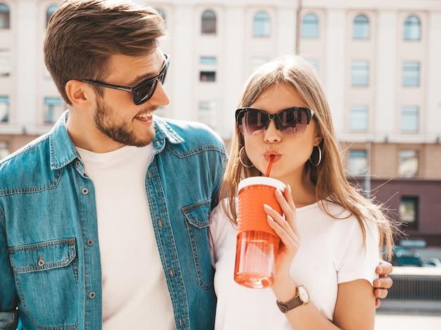 カジュアルな夏服で笑顔の美しい少女と彼女のハンサムなボーイフレンド。 。 。ストローでボトルから女性の飲料水