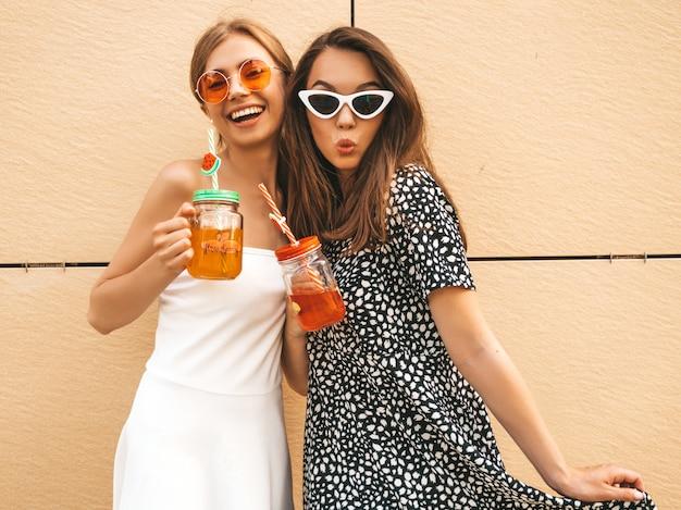 Две молодые красивые улыбающиеся битник девушки в модных летних платьях.