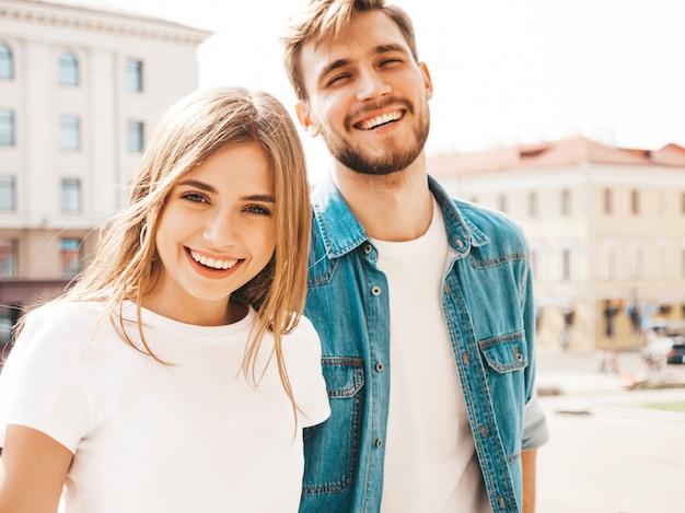 笑顔の美しい少女とカジュアルな夏服で彼女のハンサムなボーイフレンドの肖像画。 。ハグ