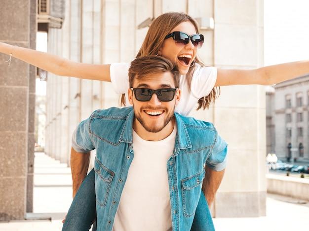 Улыбка красивая девушка и ее красивый парень в повседневной летней одежде. мужчина несет свою подругу на спине и она поднимает руки.
