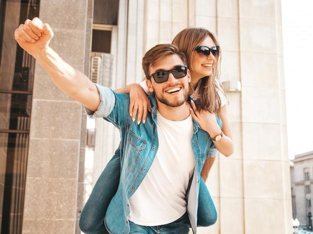 カジュアルな夏服で笑顔の美しい少女と彼女のハンサムなボーイフレンド。彼のガールフレンドを背負って彼女の手を上げる男。