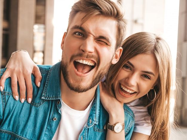 笑顔の美しい少女と彼女のハンサムなボーイフレンドの肖像画。カジュアルな夏のジーンズ服の女性。 。ウインク