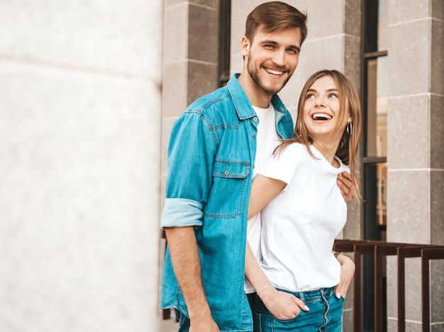 笑顔の美しい少女と彼女のハンサムなボーイフレンドの肖像画。カジュアルな夏のジーンズ服の女性。 。ハグ