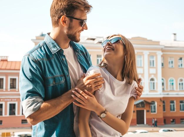 笑顔の美しい少女と彼女のハンサムなボーイフレンド。カジュアルな夏のジーンズ服の女性。お互いを見て