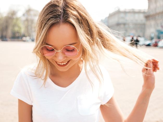 夏の流行に敏感な服に身を包んだ美しい笑顔金髪モデルの肖像画。丸いサングラスの通りでポーズをとってトレンディな女の子。楽しくて面白い女性