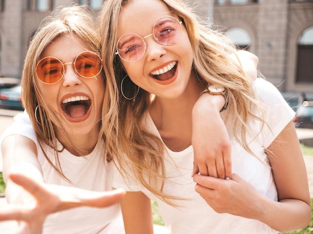 Две молодые красивые белокурые улыбающиеся хипстерские девочки в модной летней белой футболке одеваются.