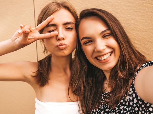 Две молодые улыбающиеся женщины битник в летней одежде.