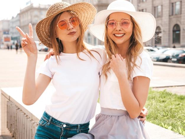 Портрет двух молодых красивых белокурых улыбающихся хипстерских девочек в модной летней белой футболке одевается.