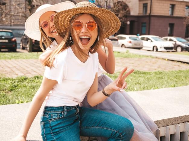 Две молодые красивые белокурые улыбающиеся хипстерские девочки в модной летней белой футболке одеваются. , , показывая мир