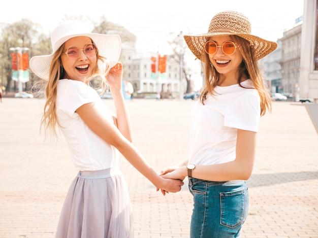 Назад двух молодых красивых белокурых улыбающихся хипстерских девочек в модной летней белой одежде футболки и шляпе. , пара, держась за руки