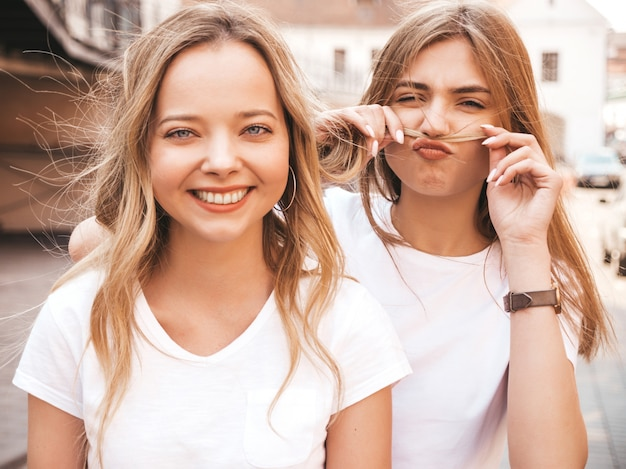Портрет двух молодых красивых белокурых улыбающихся хипстерских девочек в модной летней белой футболке одевается. , веселые позитивные модели