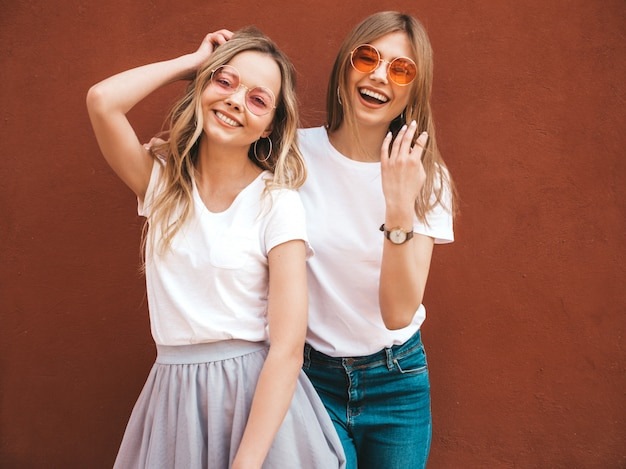 Две молодые красивые белокурые улыбающиеся хипстерские девочки в модной летней белой футболке одеваются. женщины позируют на улице возле красной стены. позитивные модели веселятся в солнечных очках