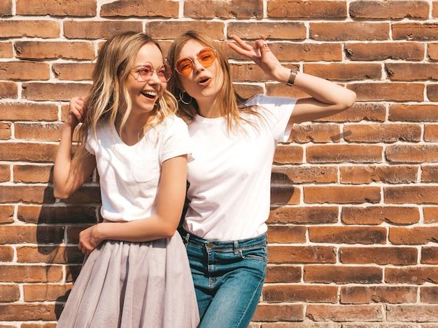 Две молодые красивые белокурые улыбающиеся хипстерские девочки в модной летней белой футболке одеваются. , позитивные модели веселятся в солнечных очках. показывает знак мира