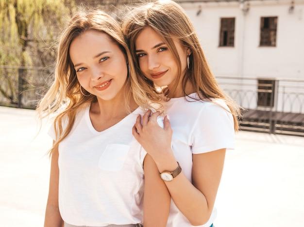 Портрет двух молодых красивых белокурых улыбающихся хипстерских девочек в модной летней белой футболке одевается. , позитивные модели с удовольствием. обниматься