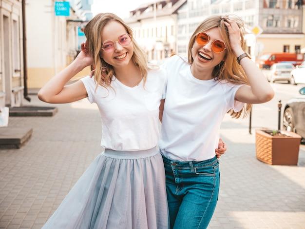 Портрет двух молодых красивых белокурых улыбающихся хипстерских девочек в модной летней белой футболке одевается. , позитивные модели веселятся в солнечных очках.