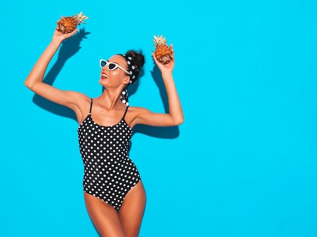 Портрет улыбается девушка брюнетка в горох купальники купальный костюм и солнцезащитные очки.
