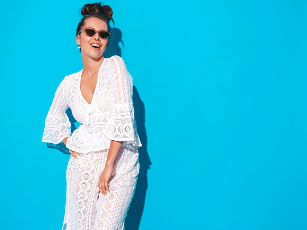 グールの髪型と若い美しいセクシーな笑顔の女性の肖像画。カジュアルな夏の白い流行に敏感なスーツでトレンディな女の子は、サングラスの服。青に分離されたホットモデル