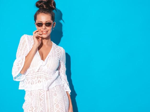 Портрет молодой красивой сексуальной усмехаясь женщины с прической вурдалака. модные девушки в случайные летние белые битник костюм одежды в солнцезащитные очки. горячая модель, изолированная на синем