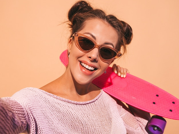 Молодая красивая сексуальная улыбающаяся хипстерская женщина в солнцезащитных очках. модная девушка в летнем вязаном кардигане. женщина с розовым пенни скейтбордом, изолированная на бежевой стене.