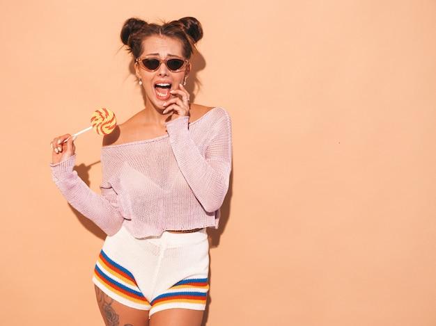 グール髪型と若い美しいセクシーな笑顔の女性のクローズアップの肖像画。サングラスでカジュアルな夏の白い水着でトレンディな女の子。ベージュに分離されたホットモデル。食べる、キャンディロリポップをかむ