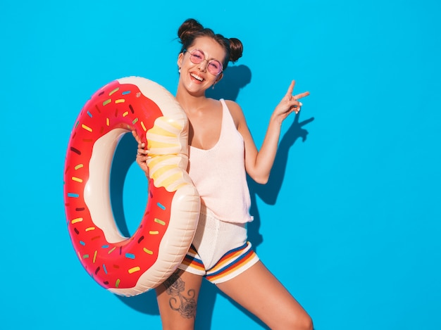 Молодая красивая сексуальная улыбается женщина битник в солнцезащитные очки. с пончиком лило надувной матрас.