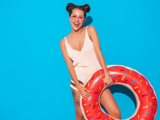 サングラスの若い美しいセクシーな笑みを浮かべて流行に敏感な女性。ドーナツリロインフレータブルマットレス付き。