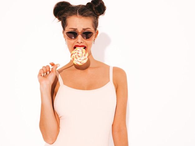 サングラスの赤い唇を持つ若い美しいセクシーな流行に敏感な女性。夏水着服のトレンディな女の子。食べる、噛むキャンディロリポップ