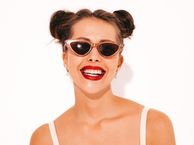 サングラスの赤い唇を持つ若い美しいセクシーな笑みを浮かべて流行に敏感な女性。