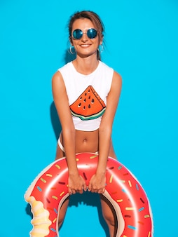 Молодая красивая улыбающаяся сексуальная женщина в солнцезащитных очках. девушка в белых летних трусах и тема с пончик лило надувной матрас.