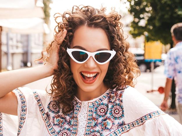 Красивая улыбающаяся модель с афро кудри прическа, одетая в летнее платье битник белое.