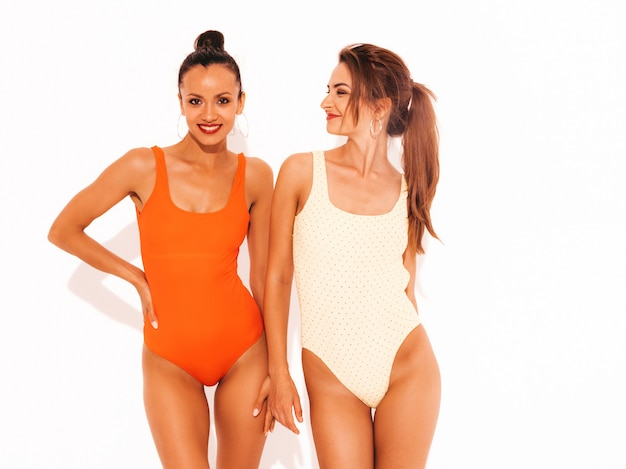 Две красивые сексуальные улыбающиеся женщины в летних разноцветных купальниках красного и желтого цвета. модные горячие модели с удовольствием. изолированные девушки