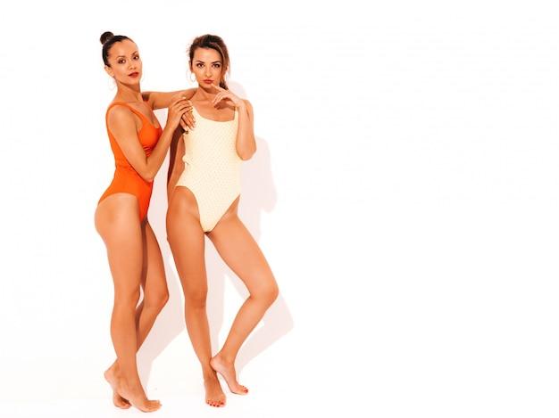 Две красивые сексуальные улыбающиеся женщины в летних разноцветных купальниках красного и желтого цвета. модные горячие модели с удовольствием. девушки изолированы. полная длина