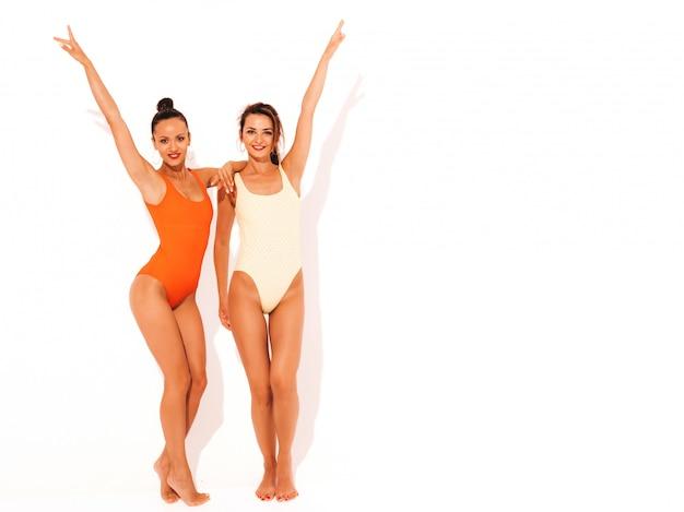Две красивые сексуальные улыбающиеся женщины в летних разноцветных купальниках красного и желтого цвета. модные горячие модели с удовольствием. девушки изолированы. полная длина. поднимать руки