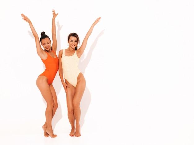 Две красивые сексуальные улыбающиеся женщины в летних разноцветных купальниках красного и желтого цвета. модные горячие модели с удовольствием. девушки изолированы. поднимать руки полная длина