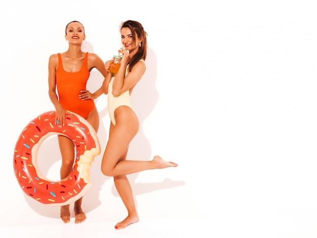 Две красивые сексуальные улыбающиеся женщины в летних разноцветных купальниках. девушки изолированы. веселые модели пьют свежий коктейль смузи напиток с надувным матрасом пончик лило
