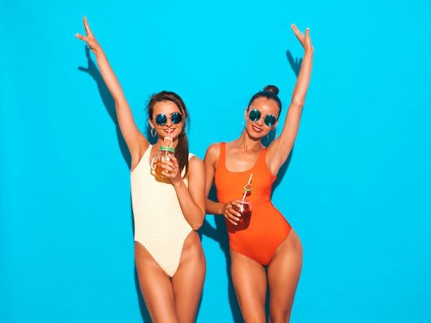 Две красивые сексуальные улыбающиеся женщины в летних разноцветных купальниках. модные девушки в солнечных очках. схожу с ума. смешные модели изолированы. пить свежий коктейль смузи напиток. поднять руки