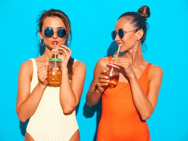 Две красивые сексуальные улыбающиеся женщины в летних разноцветных купальниках. модные девушки в солнечных очках. схожу с ума. смешные модели изолированы. пить свежий коктейль смузи напиток
