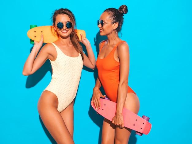Две красивые сексуальные улыбающиеся женщины в летних разноцветных купальниках. модные девушки в солнечных очках. позитивные модели веселятся с разноцветными скейтбордами. изолированные
