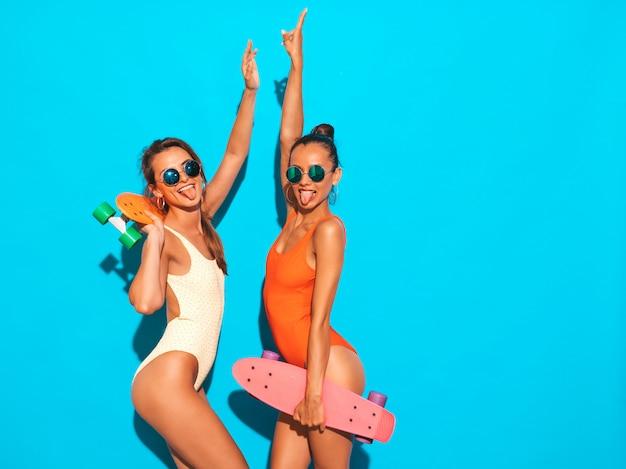 Две красивые сексуальные улыбающиеся женщины в летних разноцветных купальниках. модные девушки в солнечных очках. позитивные модели веселятся с разноцветными скейтбордами. изолированы. показывает язык