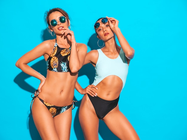 Портрет двух красивых сексуальных улыбающихся женщин в купальниках летних купальников. модные горячие модели с удовольствием. девушки в темных очках на синем фоне
