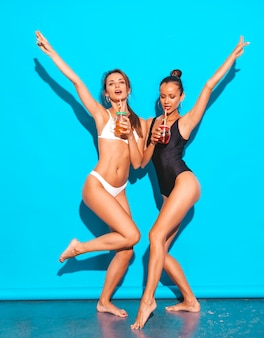Две красивые сексуальные улыбающиеся женщины в летних белых и черных купальных костюмах. модные девушки сходят с ума. смешные модели, изолированные на синем. выпить свежий коктейль смузи напиток.
