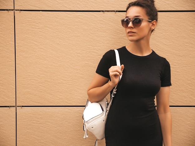 Портрет красивые улыбающиеся модели, одетые в летней одежде. модная девушка позирует на улице. веселая и позитивная женщина с удовольствием в солнцезащитных очках