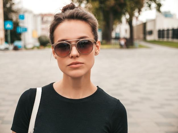 夏服に身を包んだ美しい笑顔モデルの肖像画。サングラスの通りでポーズをとってトレンディな女の子。楽しくて面白い女性