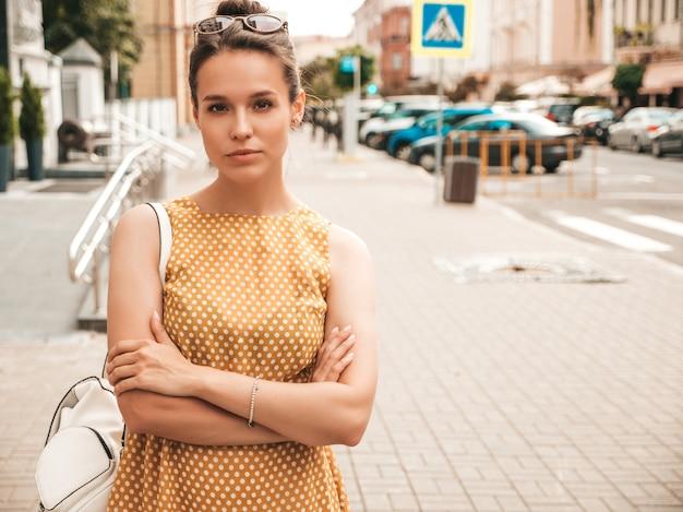 夏の黄色のドレスに身を包んだ美しい笑顔モデルの肖像画。トレンディな女の子が通りでポーズします。楽しくて面白い女性
