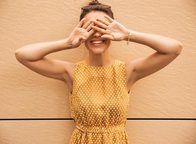 Портрет красивой улыбающейся хипстерской модели оделся в летнем желтом платье. модная девушка позирует на улице. веселая и позитивная женщина с удовольствием