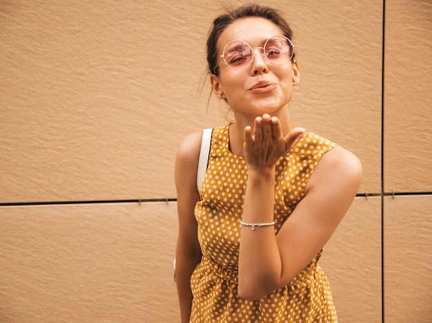 Портрет красивой улыбающейся хипстерской модели оделся в летнем желтом платье. модная девушка позирует на улице. веселая и позитивная женщина с удовольствием. дает воздушный поцелуй