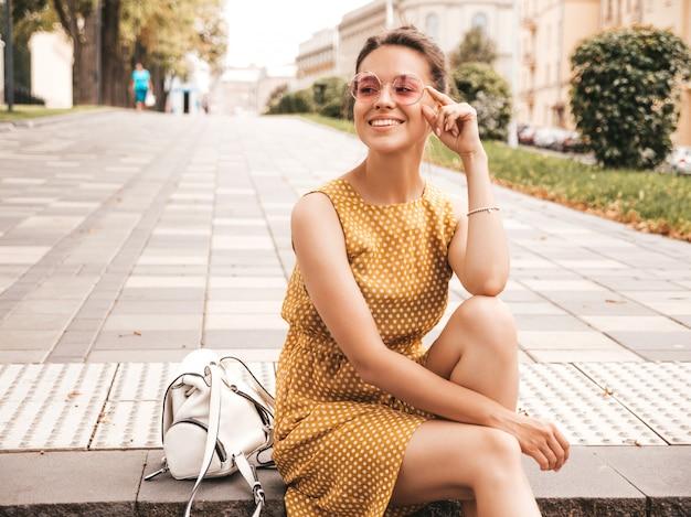 夏の黄色のドレスに身を包んだ美しい笑顔ヒップスターモデルの肖像画。トレンディな女の子が通りでポーズします。楽しくて面白い女性